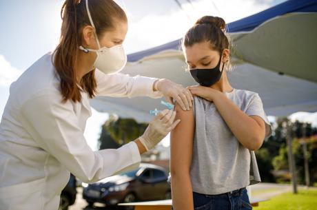 female physician vaccinates teenage girl