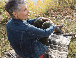 Woman sitting outside on a blanket
