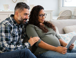 pregnant woman with husband looking at ipad on couch