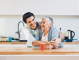 son and mother embrace in the kitchen